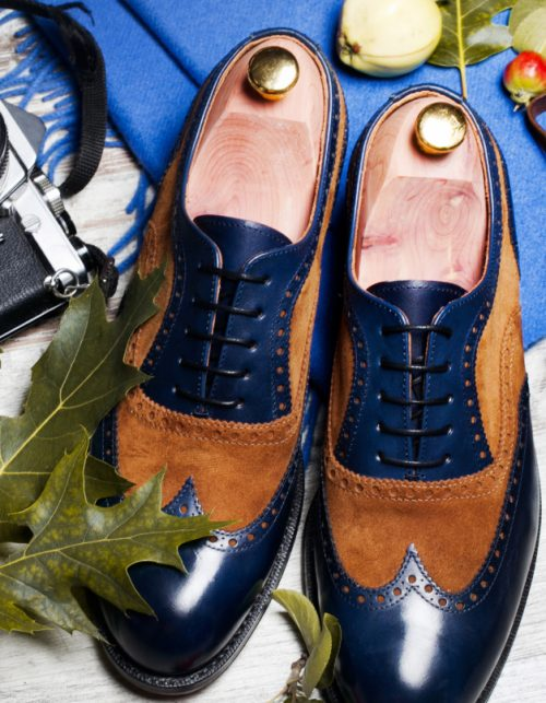 Featuring Typical Male Clothing and Accessories Still life with brown boots, leather belt and camera on aged textured boards A pair of luxury brown shoes close up on wood background